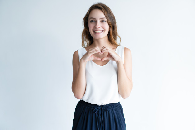 sourire-jeune-femme-faisant-geste-coeur-avec-ses-mains_1262-15259